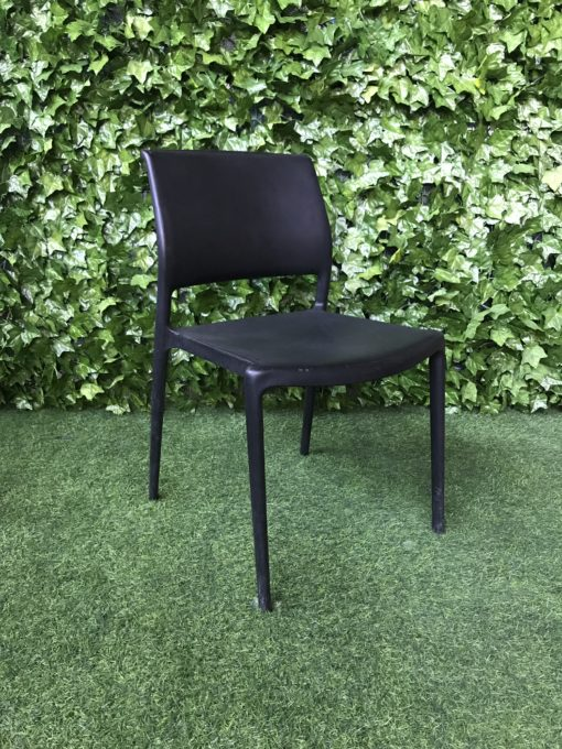 black-hard-moulded-plastic-chair-with-cut-out-low-on-the-back-and-handle-on-the-top-of-the-back-of-the-seat