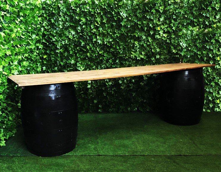 two-black-wine-barrels-with-a-3-meter-long-wooden-top-bar-for-serving-drinks-or-as-a-grazing-table