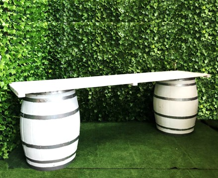 two-white-wine-barrels-with-a-3-meter-long-white-top-bar-for-serving-drinks-or-as-a-grazing-table