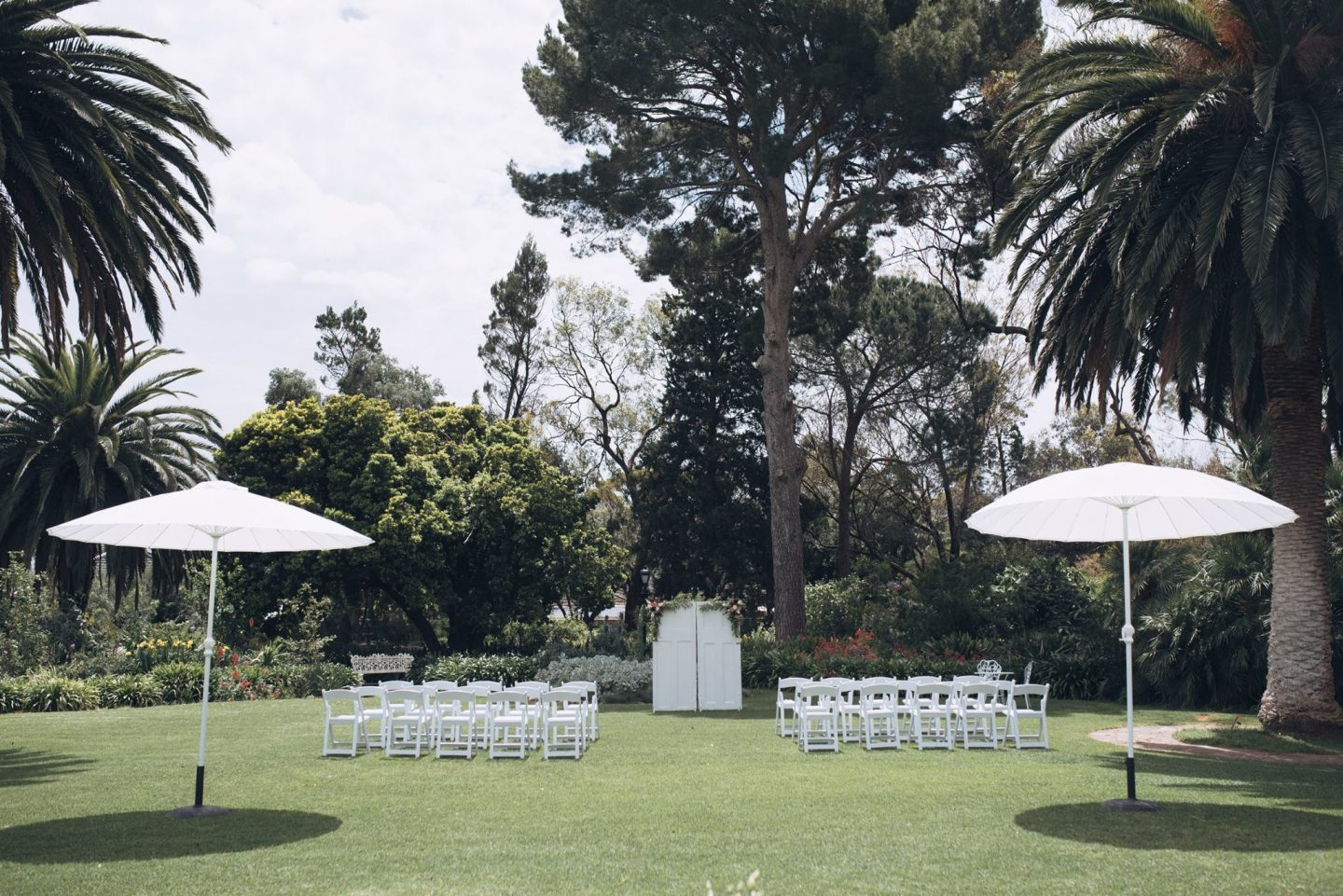 wedding-ceremony-outdoors-on-lawned-area-with-white-round-market-umbrellas-and-Americana-chairs