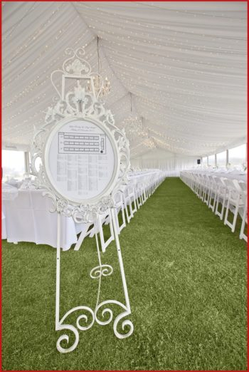 white-barouque-frame-with-seating-chart-on-white-metal-easel-with-pavilion-draping-and-wedding-table-set-up-in-the-background