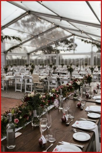 weddings stained timber table with tableware and white americana chairs-for-a-wedding-reception