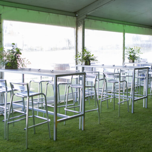 inside-a-pavilion-with-clear-walls-aluminium-bar-stools-and-slatted-high-bar-timber-tables