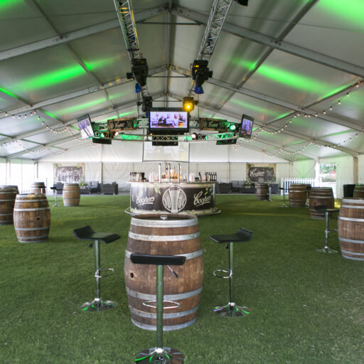 inside-a-20m-solid-roof-pavilion-with-clear-walls-wine-barrels-and-wave-stools