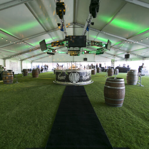 inside-a-20m-solid-roof-pavilion-with-clear-walls-black-carpet-runner-wine-barrels-and-wave-stools