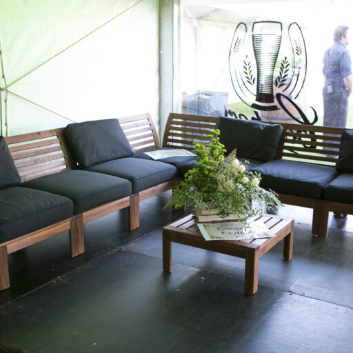 timber-wooden-lounge-setting-with-black-cushions-on-black-ply-flooring