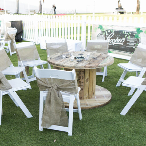 Front-area-of-coopers-retirement-party-with-white-americana-chairs-hessian-sashes-cable-tables