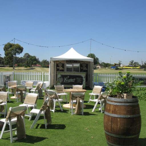 Front-area-of-coopers-retirement-party-with-white-americana-chairs-hessian-sashes-cable-tables-and-peak-top-pavilion-in-background
