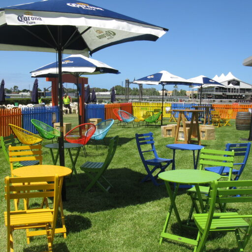 outdoor-furniture-products-in-green-yellow-and-blue-timber-outdoor-settings-table-and-chairs-with-assorted-coloured-acapulco-chairs-and-picket-fencing