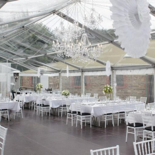 Wedding-10m-x-24m-Clear-Pavilion-with-White-Chiavari-Chairs-with-Black-Cushions-Wooden-Flooring-and-Chandeliers