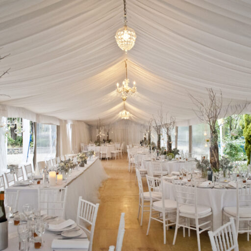 Wedding-6m-x-21m-Pavilion-with-Roof-and-Wall-Lining-Feast-Watson-Flooring-White-Chiavari-Chairs-and-Round-Tables