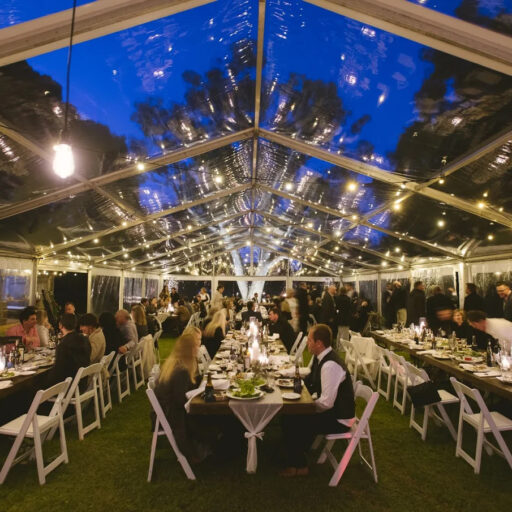 Wedding-10m-x-24m-Clear-Pavilion-with-Stained-Timber-Tables-Americanas-and-Festoon-Lighting
