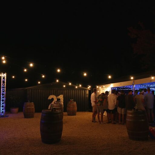 Festoon-lights-attached-to-pavilion-at-night-with-wine-barrels-and-people