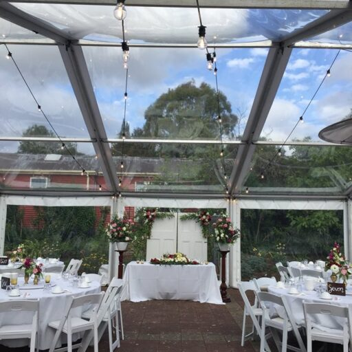 Wedding-10m-x-24m-Clear-Pavilion-with-Festoon-Lighting-Americana-Chairs-Round-Tables-and-White-Linen-at-Beaumont-House