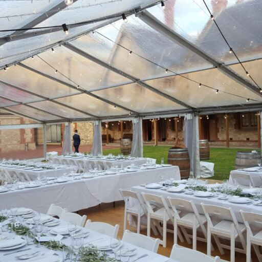 Wedding-at-Armoury-Lawns-10m-x-21m-Clear-Pavilion-with-Americana-Chairs-White-Linen-Wine-Barrels-Feast-Watson-Flooring-and-Festoon-lights