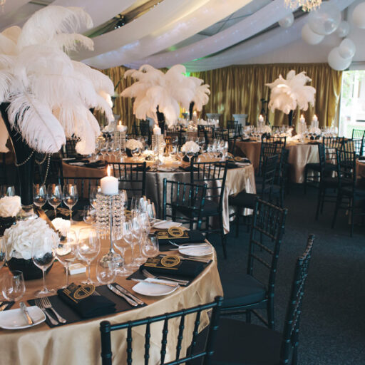 room-with-wall-and-roof-linen-drapining-round-tables-with-gold-and-black-table-decor-with-black-chiavari-chairs