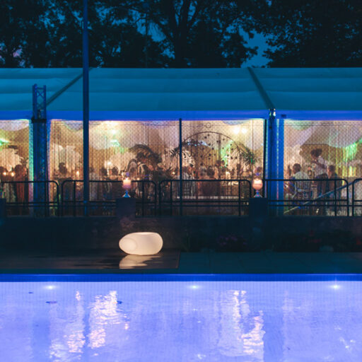 pavilion-with-solid-white-vinyl-roof-and-clear-walls-lit-up-at-night-by-the-pool