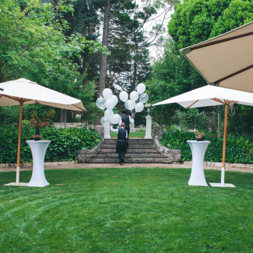 green-lawn-area-with-white-square-market-umbrellas-and-round-aluminium-bar-tables-with-white-lycra-covers-as-entrance-for-a-birthday