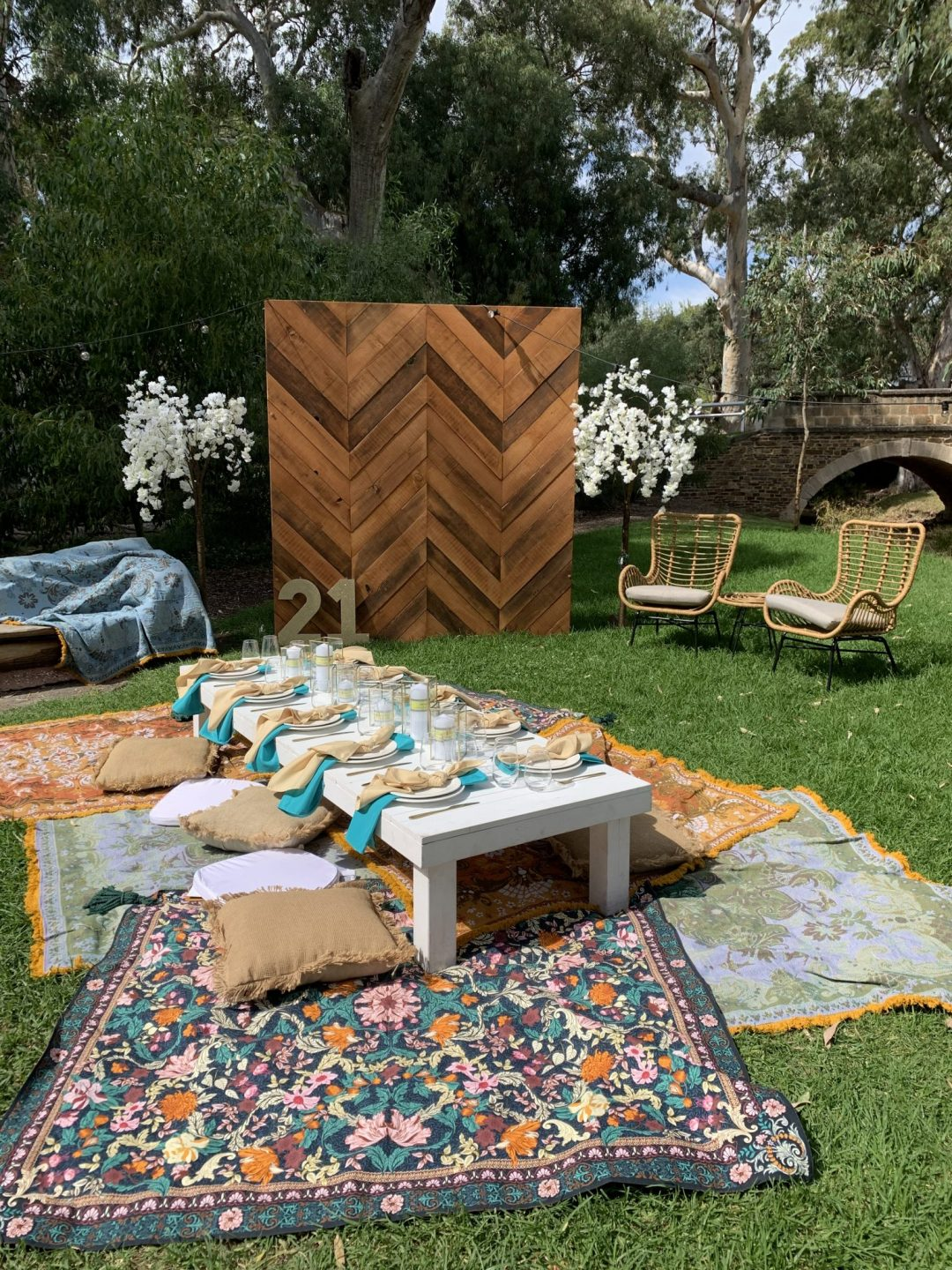 overhead-view-of-picnic-package-with-white-pallet-picnic-table-glass-candle-boxes-with-champagne-and-turquoise-linen-napkins-AFC-crockery-and-standard-glassware-assorted-cushions-and-wandering-folk-rugs