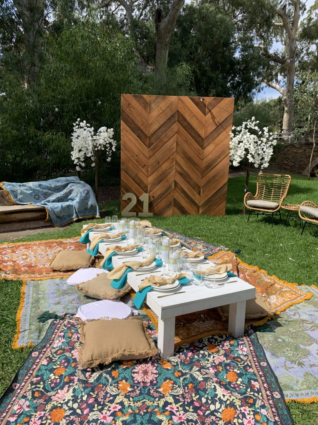 picnic-package-with-white-pallet-picnic-table-glass-candle-boxes-with-champagne-and-turquoise-linen-napkins-AFC-crockery-and-standard-glassware-assorted-cushions-and-wandering-folk-rugs