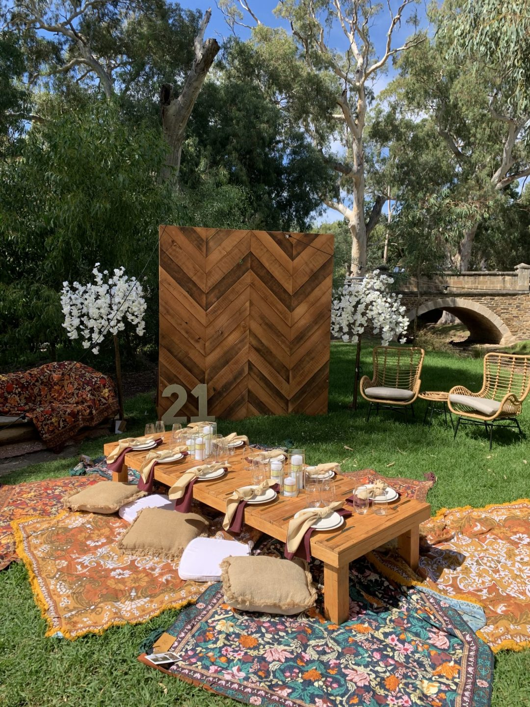 picnic-package-with-rustic-pallet-picnic-table-glass-candle-boxes-with-champagne-and-burgundy-linen-napkins-AFC-crockery-and-standard-glassware-assorted-cushions-and-wandering-folk-rugs