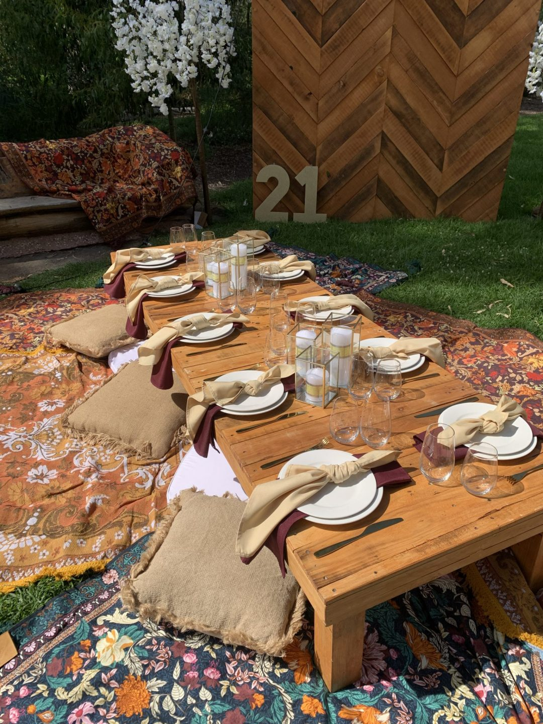 rustic-pallet-picnic-table-glass-candle-boxes-with-champagne-and-burgundy-linen-napkins-AFC-crockery-and-standard-glassware-assorted-cushions-and-wandering-folk-rugs