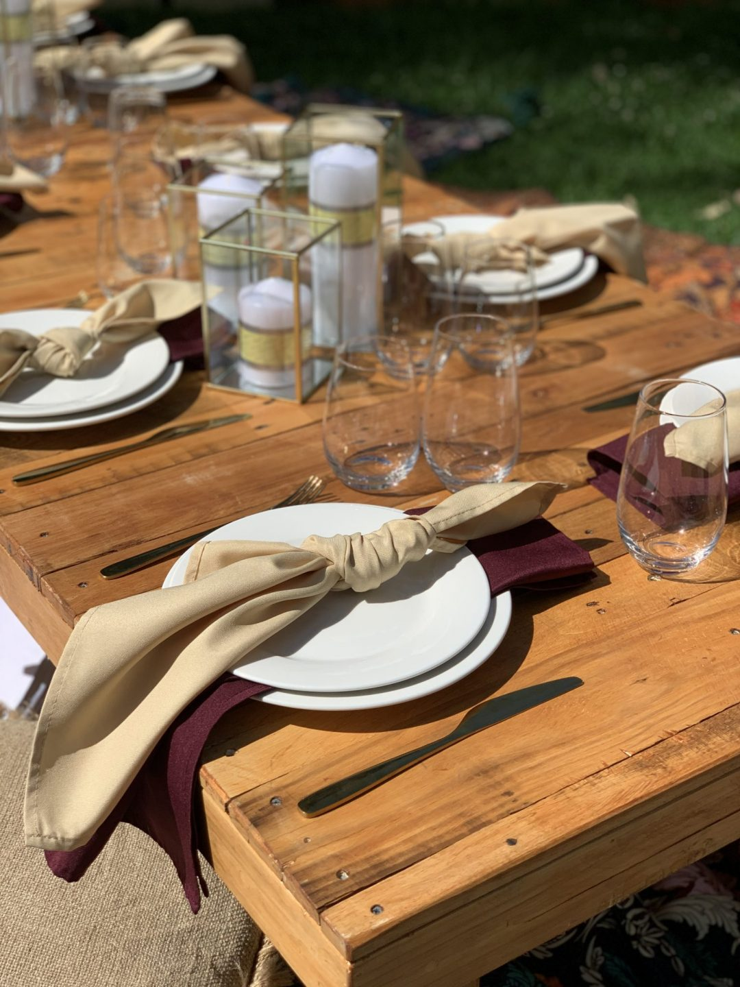 close-up-on-rustic-pallet-picnic-table-with-champagne-and-burgundy-linen-napkins-AFC-crockery-and-standard-glassware
