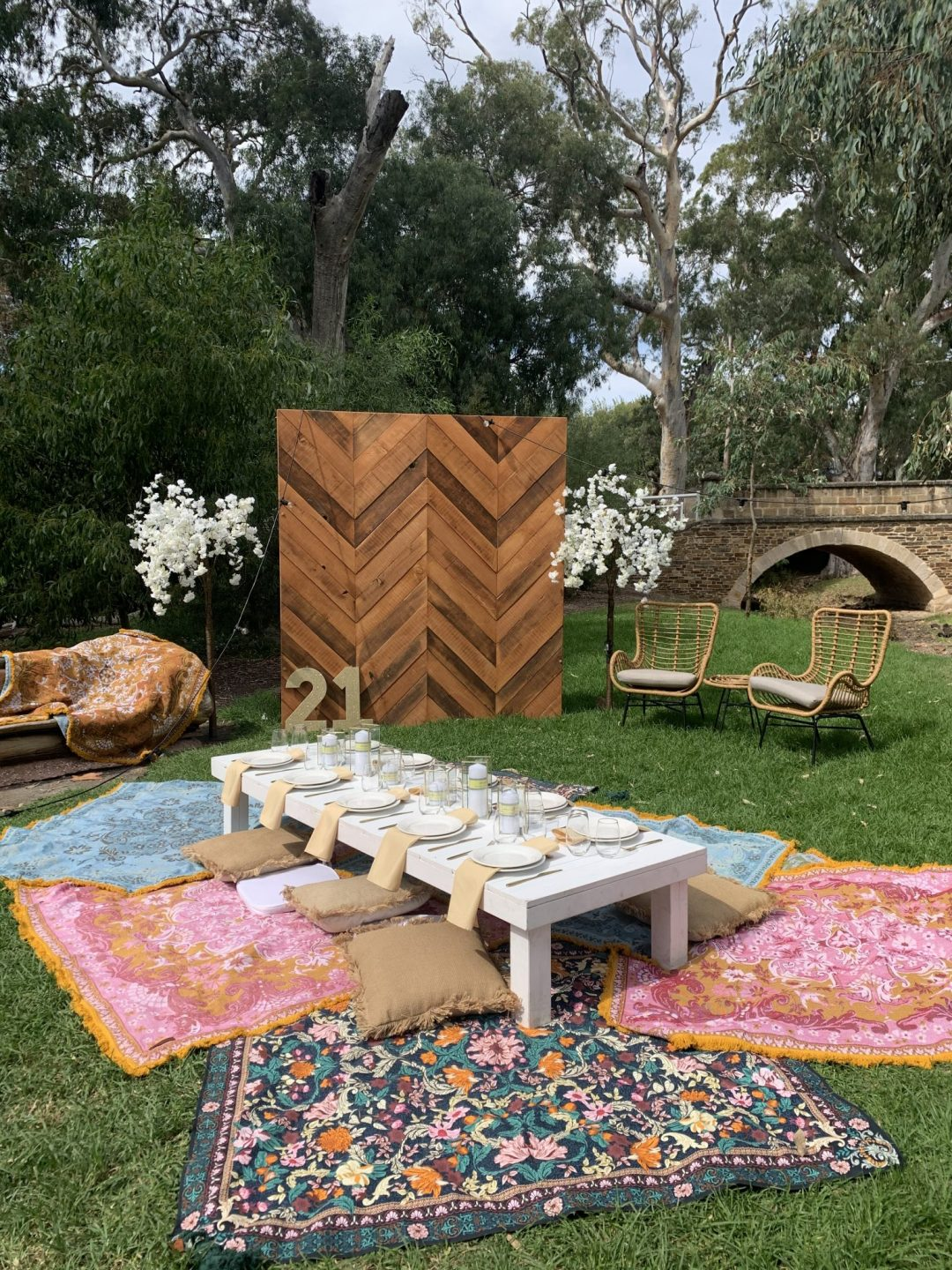 picnic-package-with-white-pallet-picnic-table-glass-candle-boxes-with-champagne-linen-napkins-AFC-crockery-and-standard-glassware-assorted-cushions-and-wandering-folk-rugs