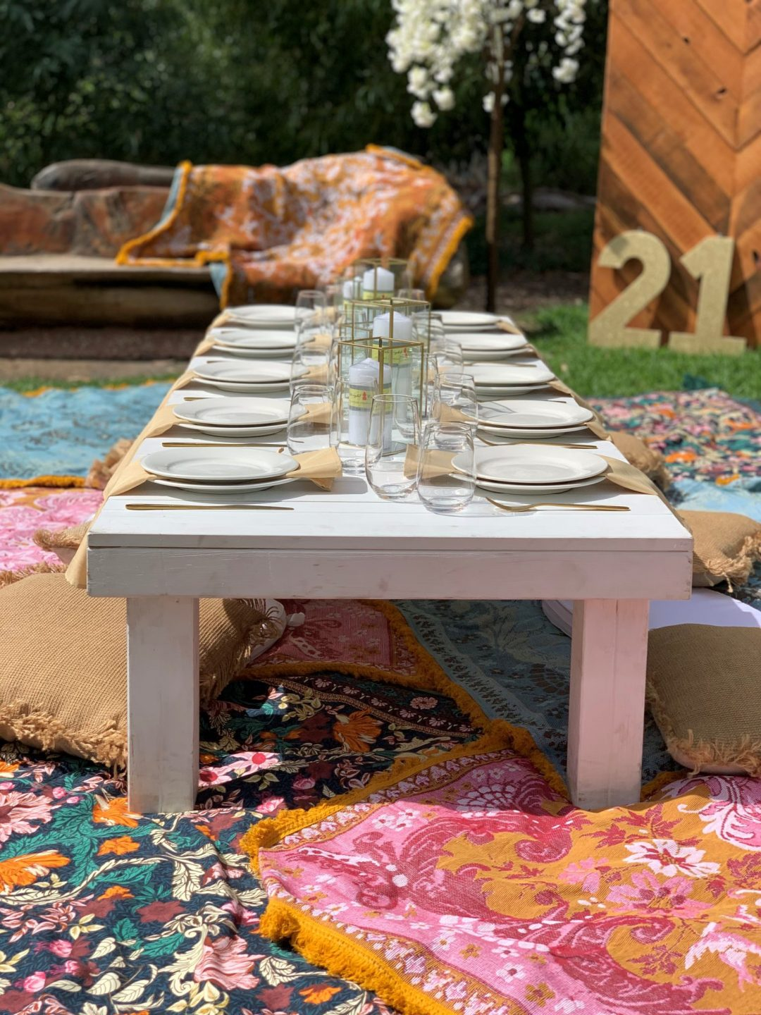 white-pallet-picnic-table-glass-candle-boxes-with-champagne-linen-napkins-AFC-crockery-and-standard-glassware-assorted-cushions-and-wandering-folk-rugs