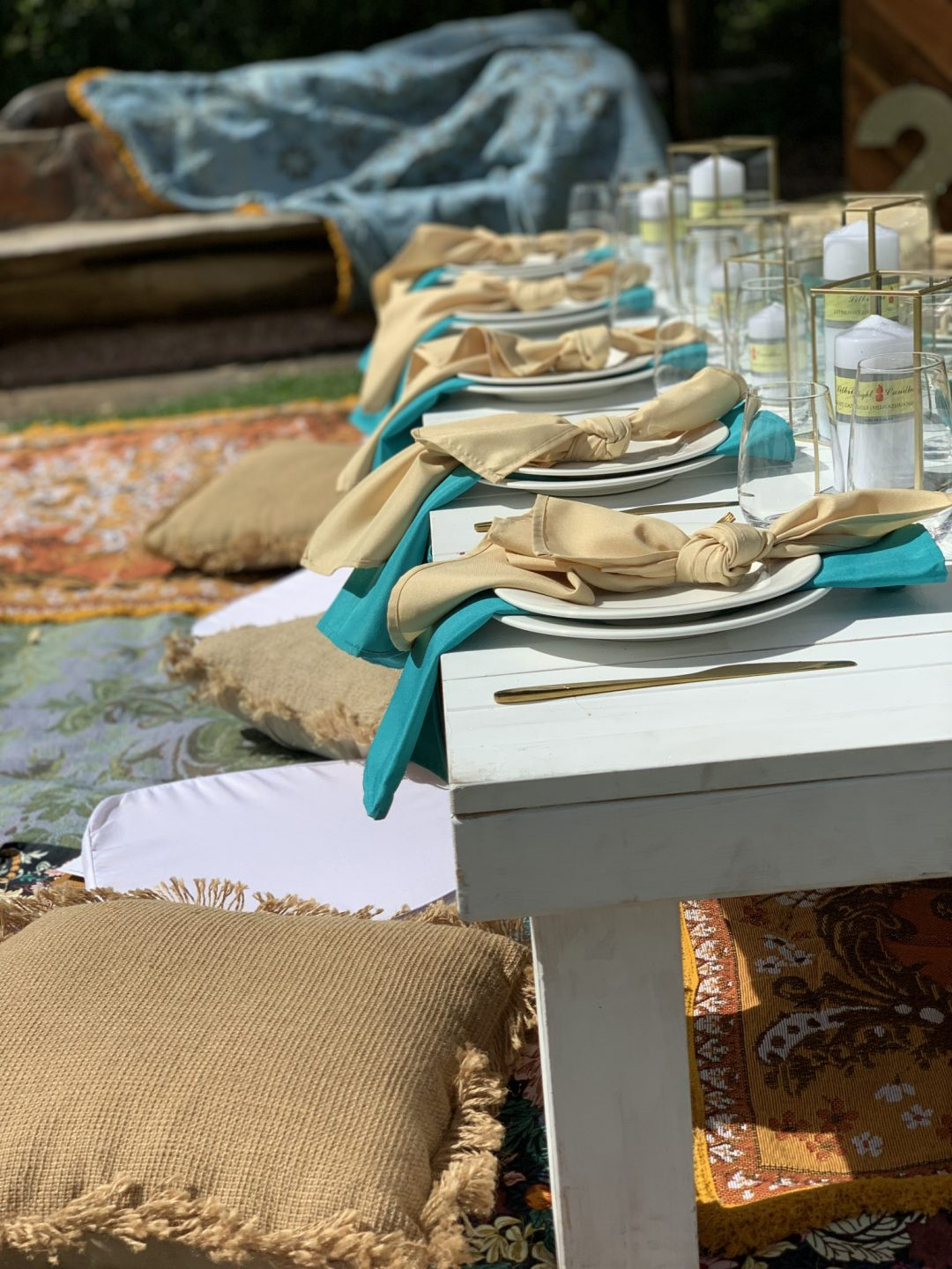 white-pallet-picnic-table-glass-candle-boxes-with-champagne-and-turquoise-linen-napkins-AFC-crockery-and-standard-glassware-assorted-cushions-and-wandering-folk-rugs