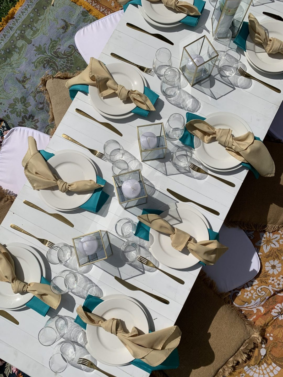 overhead-view-of-white-pallet-picnic-table-glass-candle-boxes-with-champagne-and-turquoise-linen-napkins-AFC-crockery-and-standard-glassware-assorted-cushions-and-wandering-folk-rugs