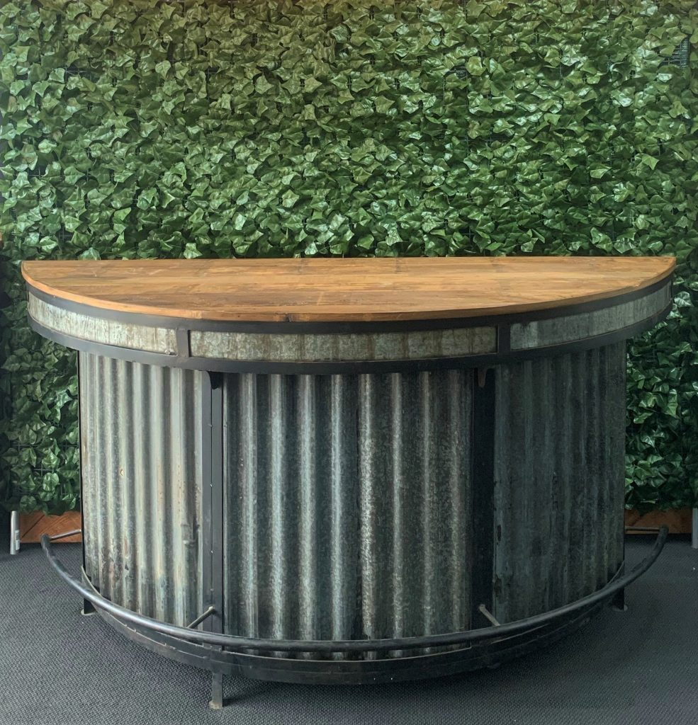curved-wooden-top-and-corrugated-iron-bar-with-black-metal-frame-detailing-and-foot-rest